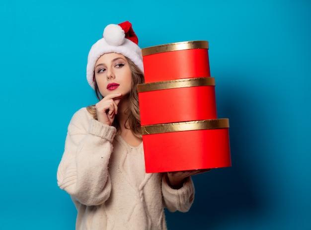 Mulher bonita com caixa de presente na parede azul