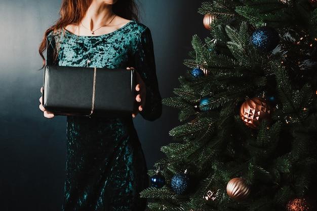Mulher bonita com caixa de presente perto de árvore de natal