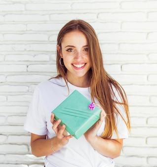 Mulher bonita com caixa de presente verde olhando para a câmera