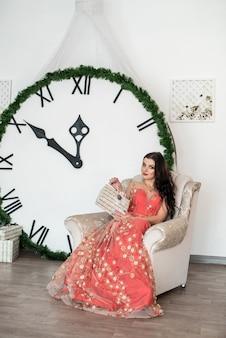 Mulher bonita com caixas de presentes sentada na cadeira