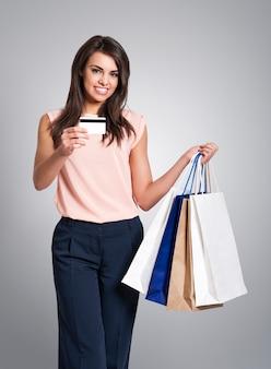 Mulher bonita com cartão de crédito e sacolas de compras