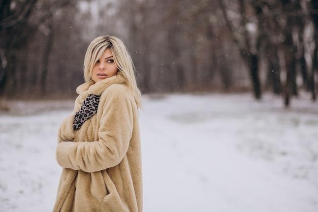 Mulher bonita com casaco de inverno caminhando em um parque cheio de neve