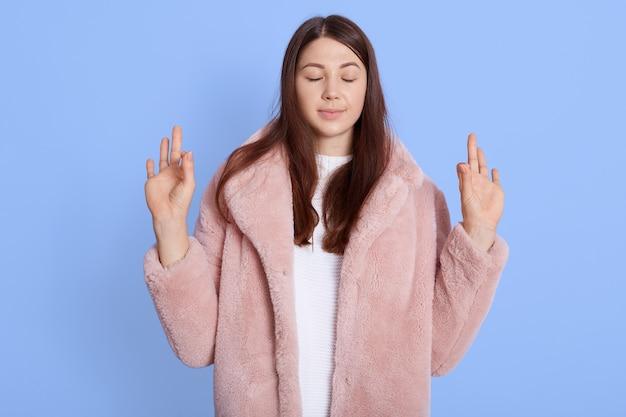 Mulher bonita com casaco de pele falsa rosa mostrando sinal de ok