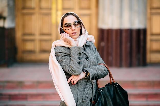 Mulher bonita com casaco falando ao telefone na rua