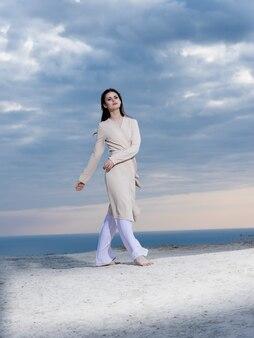 Mulher bonita com casaco posando de ar fresco de praia estilo elegante