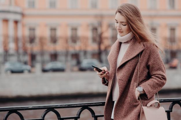 Mulher bonita com casaco quente, possui telefone celular moderno, mensagens em redes sociais