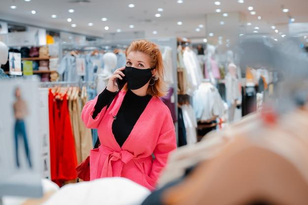 Mulher bonita com casaco rosa brilhante shopping shopping telefone com máscara protetora preta