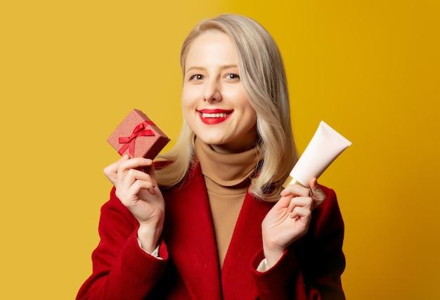 Mulher bonita com casaco vermelho com caixa de presente e tubo de creme na parede amarela