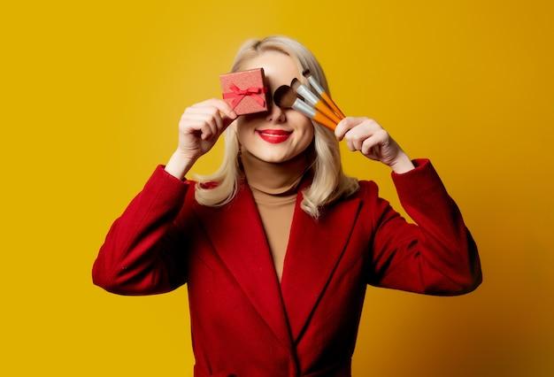 Mulher bonita com casaco vermelho com pincéis e caixa de presente na parede amarela