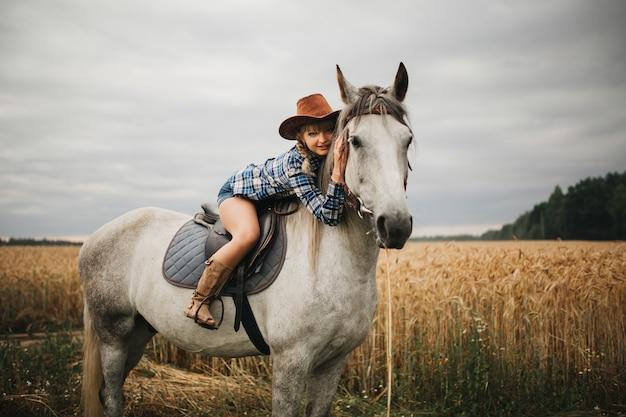 Mulher bonita com cavalo castanho no campo à noite