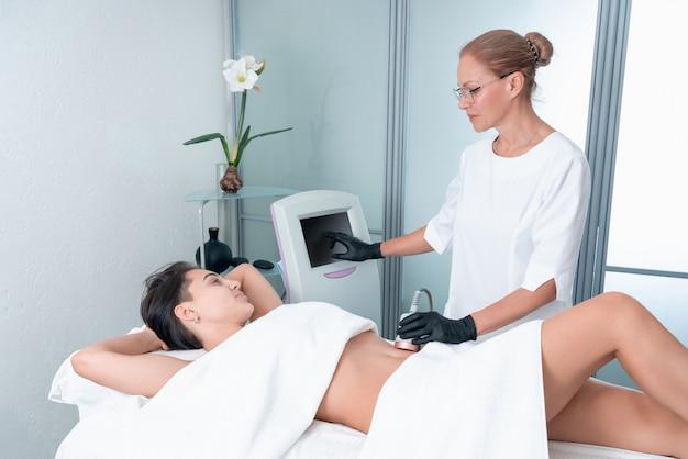 Mulher bonita com cavitação, procedimento de remoção de celulite nas pernas e barriga na clínica de beleza