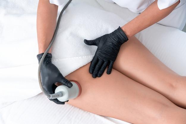 Mulher bonita com cavitação, procedimento de remoção de celulite nas pernas em uma clínica de beleza