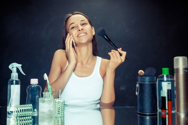 Mulher bonita com celular aplicando maquiagem