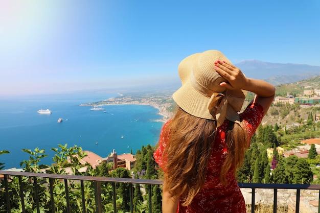 Mulher bonita com chapéu, apreciando a vista do vulcão etna de taormina, na sicília, itália