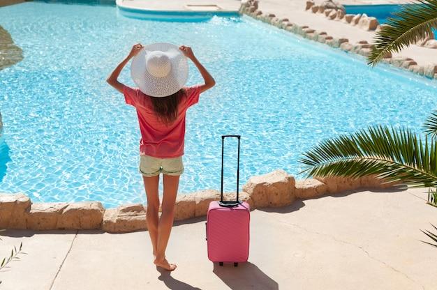 Mulher bonita com chapéu branco perto da área da piscina do hotel com mala rosa. viagem, férias de verão e férias