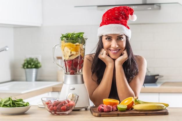Mulher bonita com chapéu de natal na cozinha, rodeada por muitas frutas e folhas de espinafre para um smoothie.