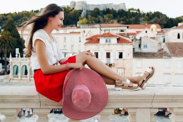 Mulher bonita com chapéu vermelho nas pernas de férias em sandálias