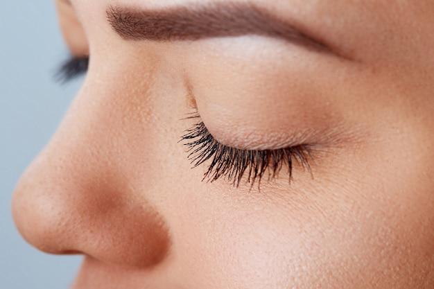 Mulher bonita com cílios longos em um salão de beleza. procedimento de extensão de cílios. cosméticos e maquiagem.