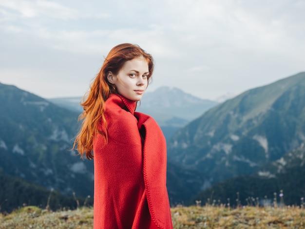 Mulher bonita com cobertor quente nas montanhas e modelo de cabelo vermelho.