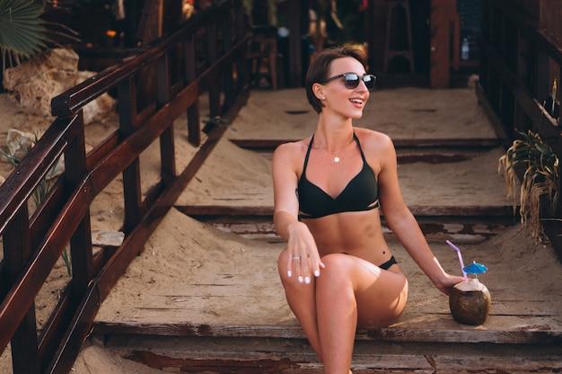 Mulher bonita com coco sentado na escada no bar