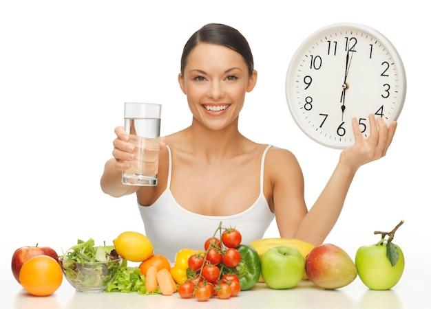 Mulher bonita com comida saudável água e relógio
