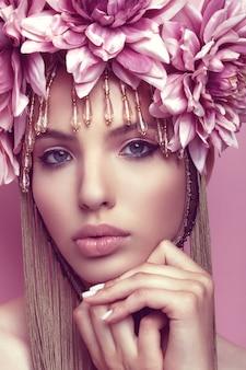 Mulher bonita com coroa de flores e maquiagem segurando a mão sob o queixo