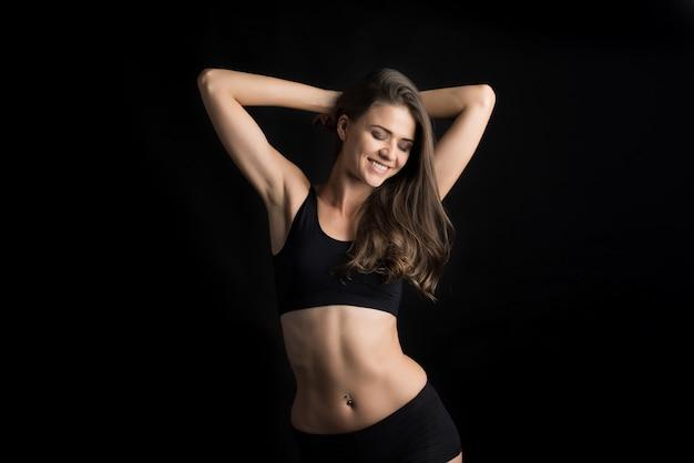Mulher bonita com corpo saudável em fundo preto