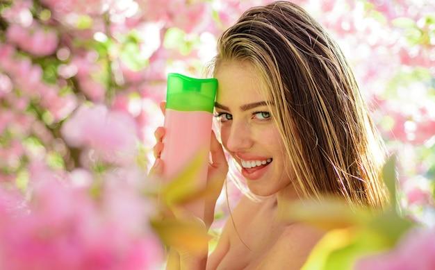 Mulher bonita com cosméticos à base de plantas da natureza para cabelos, cuidados com os cabelos, xampu, bálsamo, condicionador.