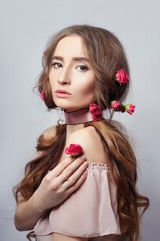 Mulher bonita com cosméticos de flores rosas