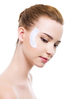 Mulher bonita com creme hidratante cosmético no rosto - branco