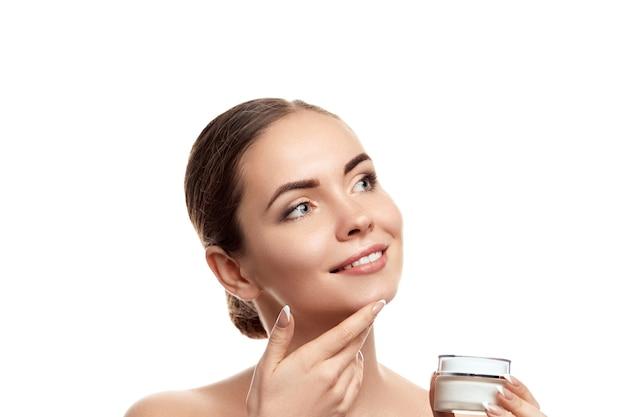 Mulher bonita com creme hidratante. retrato de mulher com pele limpa. cuidados com a pele. cosméticos. tratamento facial. cosmetologia, beleza e spa