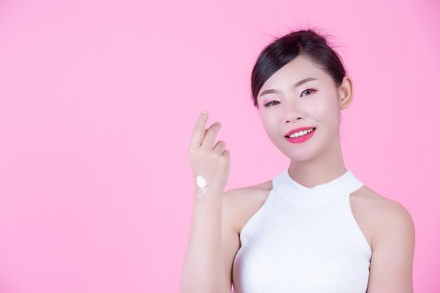 Mulher bonita com creme na pele em um fundo cor-de-rosa.
