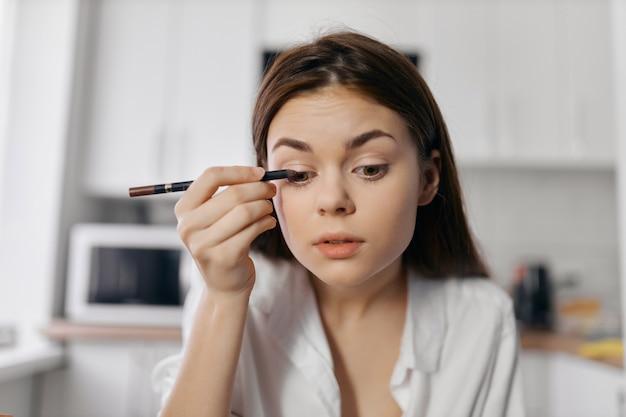 Mulher bonita com delineador, lápis, maquiagem, sala de cosmetologia