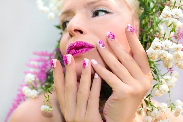 Mulher bonita com desenho de flor rosa de verão astilbe nos lábios e nos dedos
