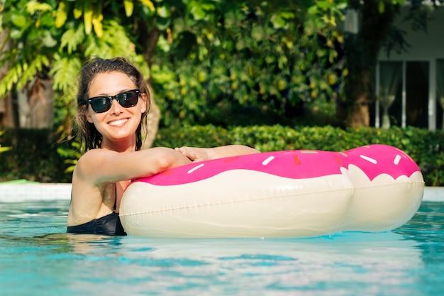 Mulher bonita com donut inflável na piscina