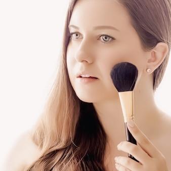 Mulher bonita com escova de maquiagem, pele perfeita e cabelo brilhante como maquiagem, saúde e bem-estar, retrato do rosto de uma jovem modelo feminina para cosméticos para a pele e design de anúncio de beleza de luxo