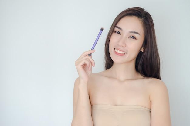 Mulher bonita com escova de pó cosmético para fazer as pazes. linda garota asiática mostra sua pele perfeita