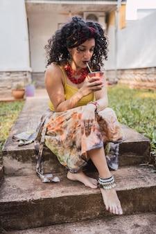 Mulher bonita com estilo cigano, bebendo chá mate.