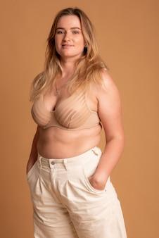 Mulher bonita com excesso de peso em maiô bege em fundo rosa