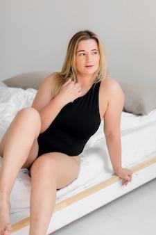 Mulher bonita com excesso de peso em maiô preto sobre fundo branco