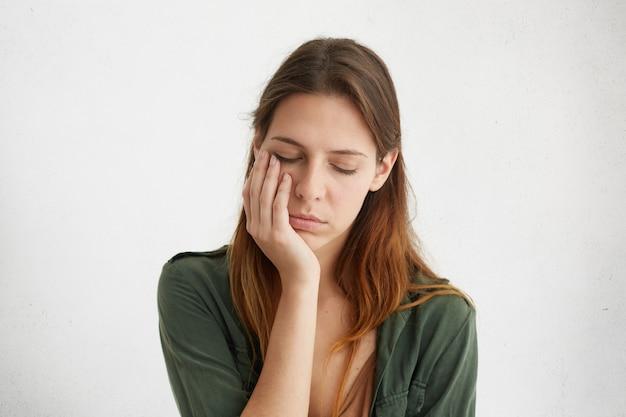 Mulher bonita com expressão sonolenta, parecendo cansada, segurando a mão na bochecha, fechando os olhos de cansaço.