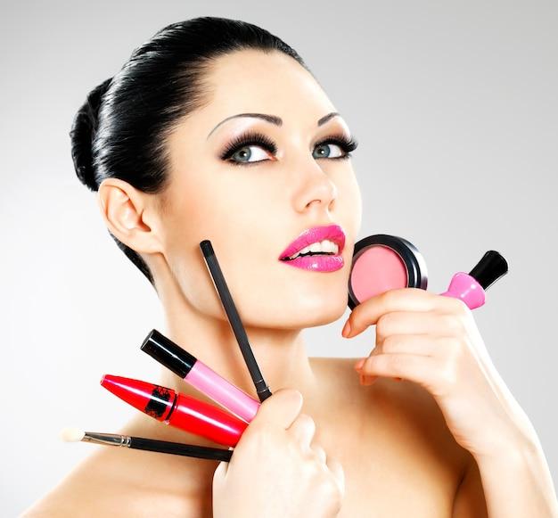 Mulher bonita com ferramentas de maquiagem cosmética perto de seu rosto.