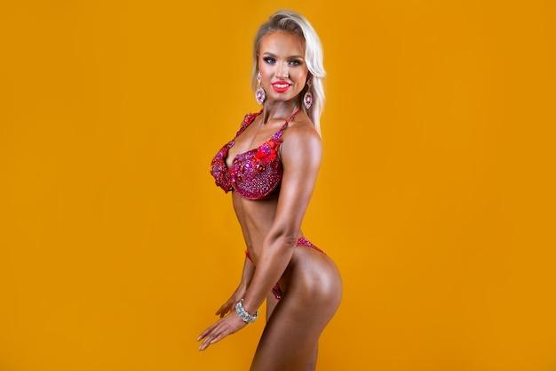 Mulher bonita com figura atlética atlética com músculos em um maiô