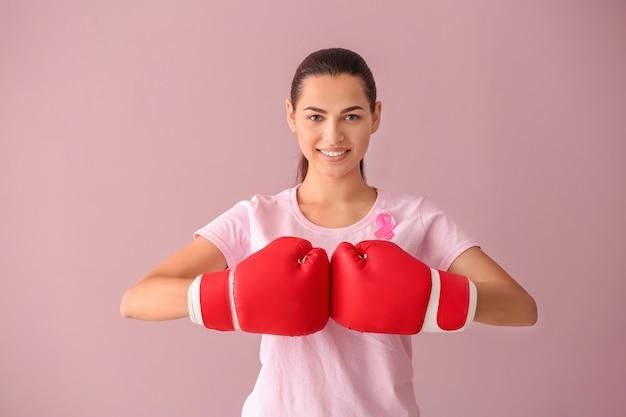 Mulher bonita com fita rosa e luvas de boxe na cor de fundo. conceito de câncer de mama