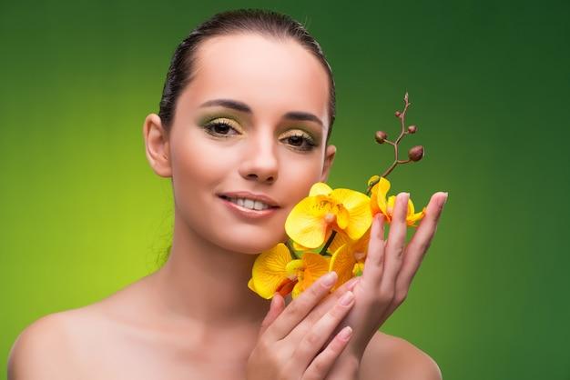 Mulher bonita com flor de orquídea amarela