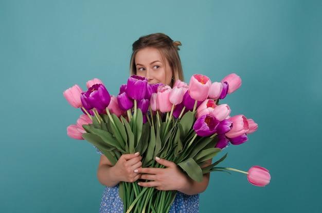 Mulher bonita com flores. bela jovem com ramo de flores nas mãos dela. férias de primavera e verão. dia da mulher. beleza, conceito de moda.