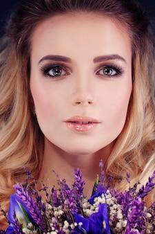Mulher bonita com flores. closeup de rosto bonito. maquiagem e penteado loiro