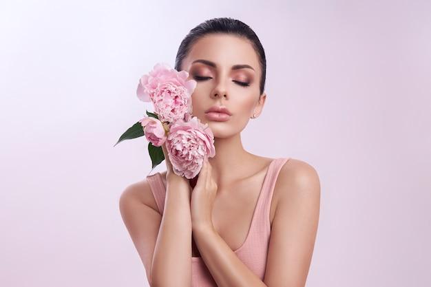 Mulher bonita com flores de peônia rosa