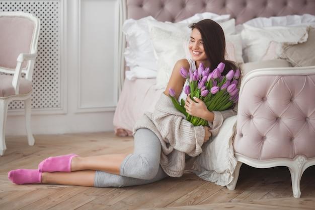 Mulher bonita com flores dentro de casa
