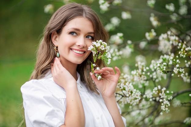 Mulher bonita com flores desabrochando da primavera em uma árvore.
